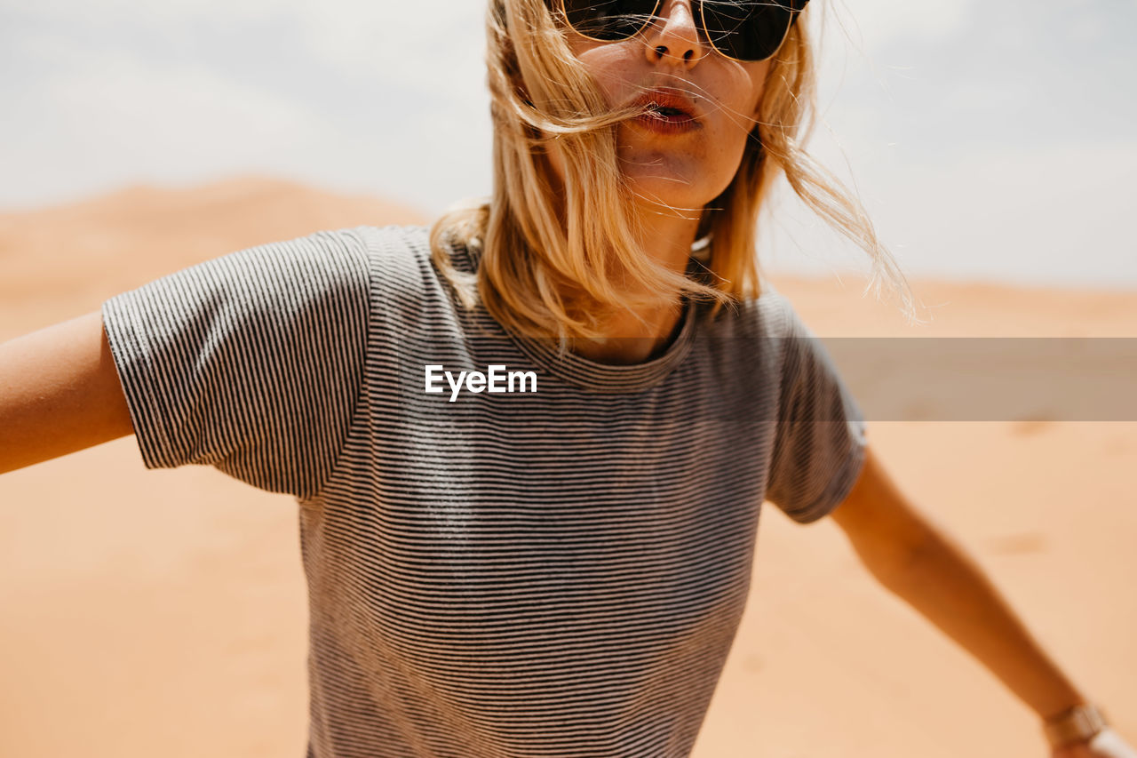 Portrait Of Woman In Sunglasses Standing On Desert In Sunny Day