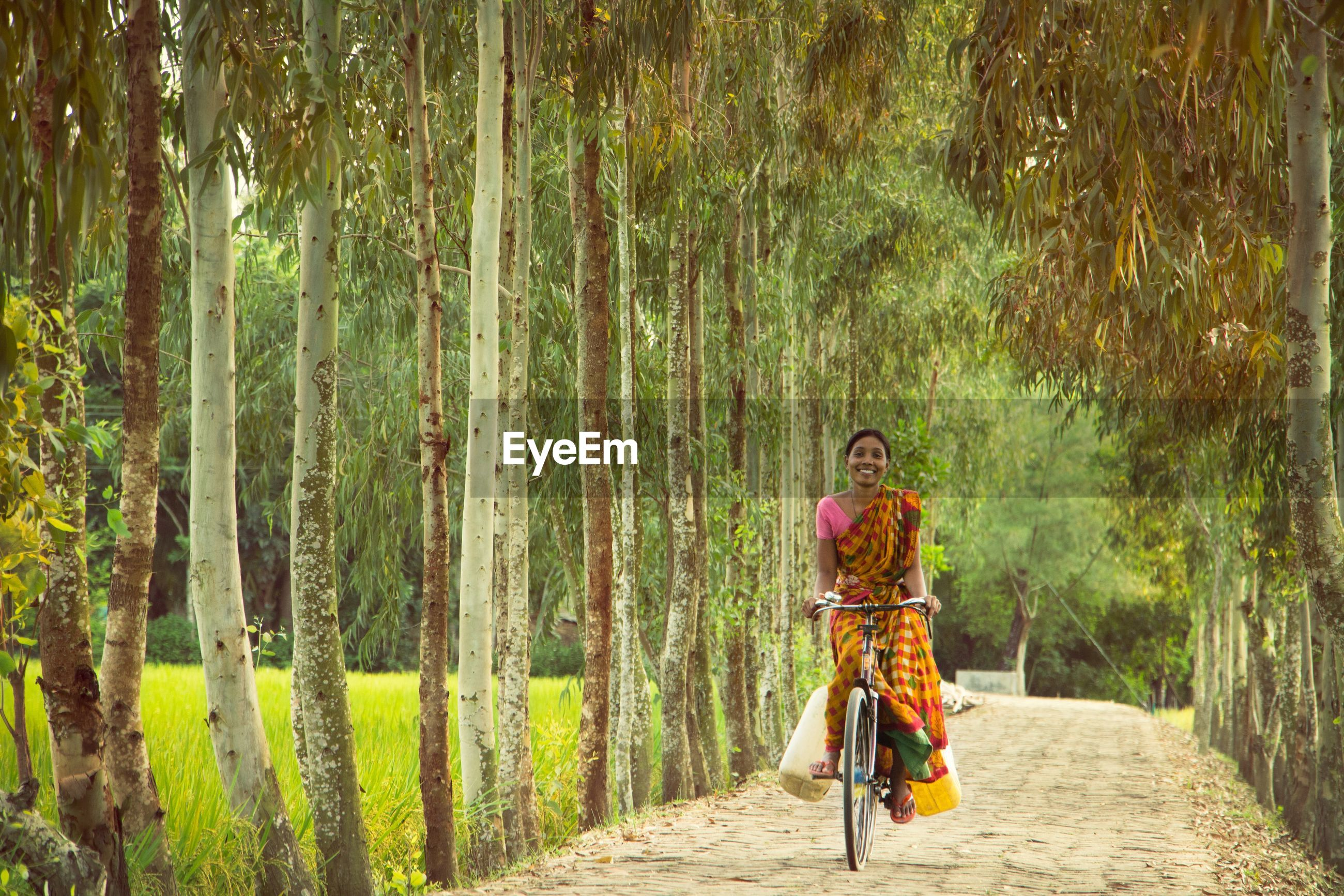 MAN RIDING BICYCLE ON ROAD IN FOREST