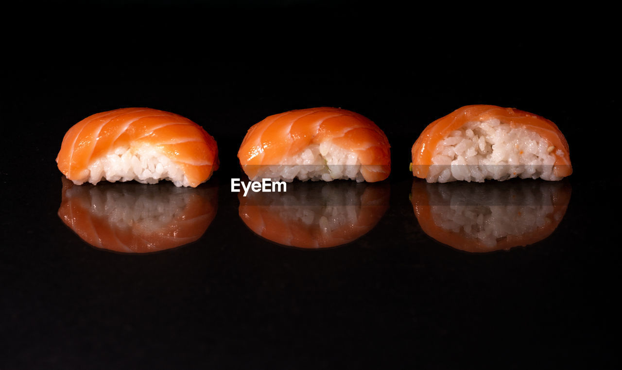 CLOSE-UP OF SUSHI IN BLACK BACKGROUND