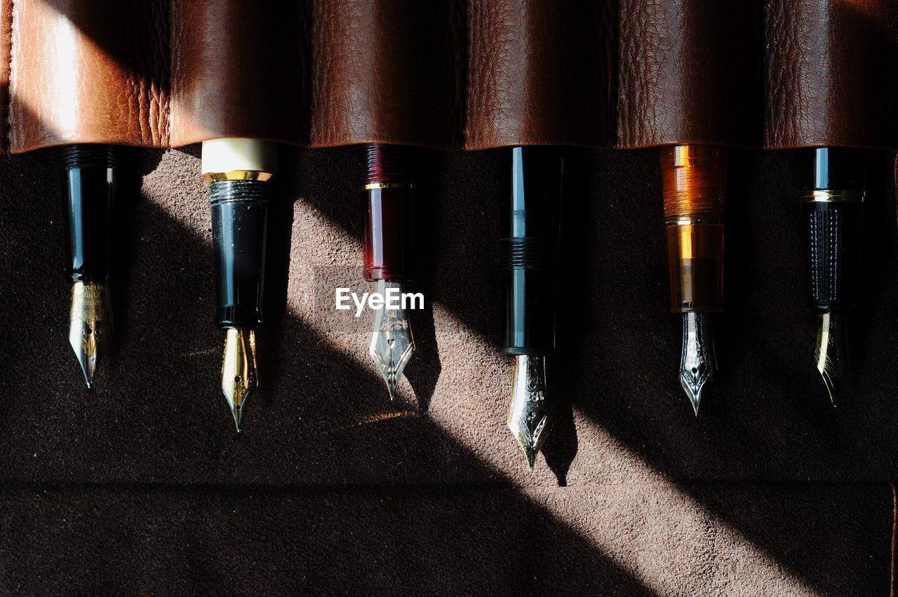 Directly above shot of fountain pens in leather on table