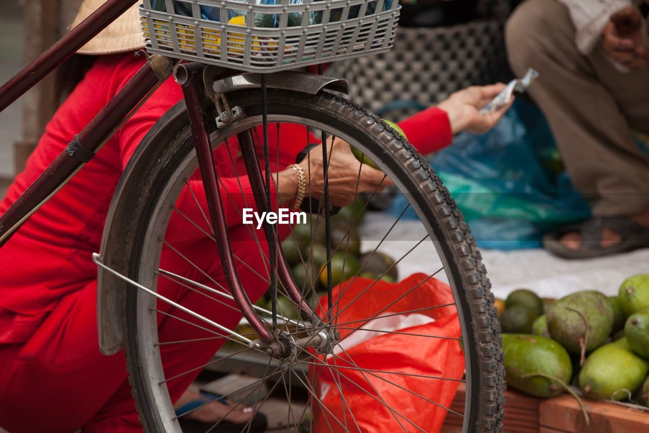transportation, bicycle, land vehicle, mode of transportation, focus on foreground, wheel, retail, day, real people, small business, men, basket, one person, low section, container, healthy eating, incidental people, fruit, outdoors, spoke