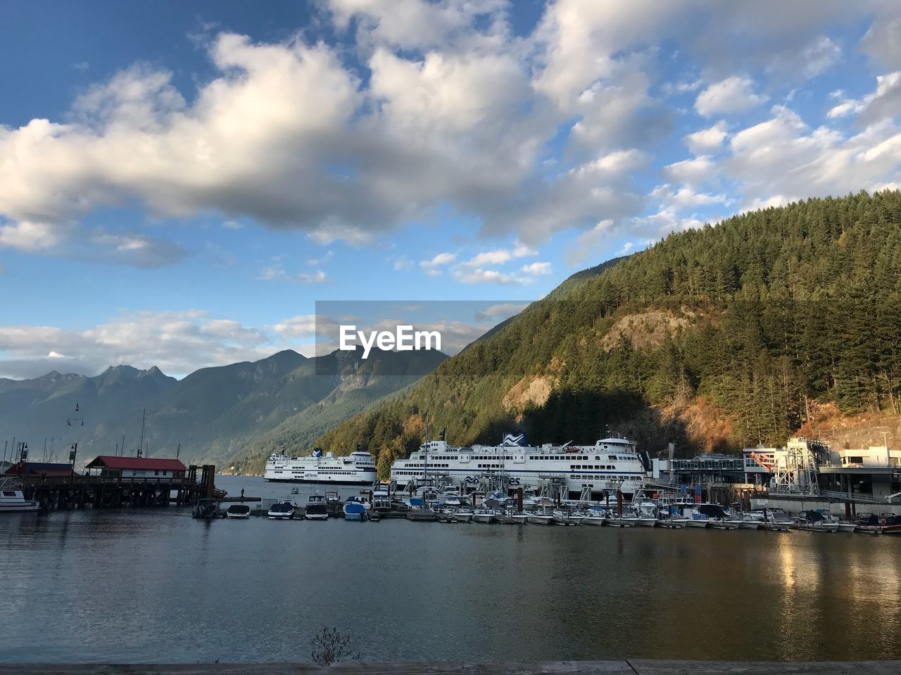 water, cloud - sky, mountain, sky, nautical vessel, waterfront, transportation, architecture, built structure, mode of transportation, nature, scenics - nature, building exterior, no people, beauty in nature, river, tree, harbor, outdoors, mountain range, yacht, passenger craft, bay
