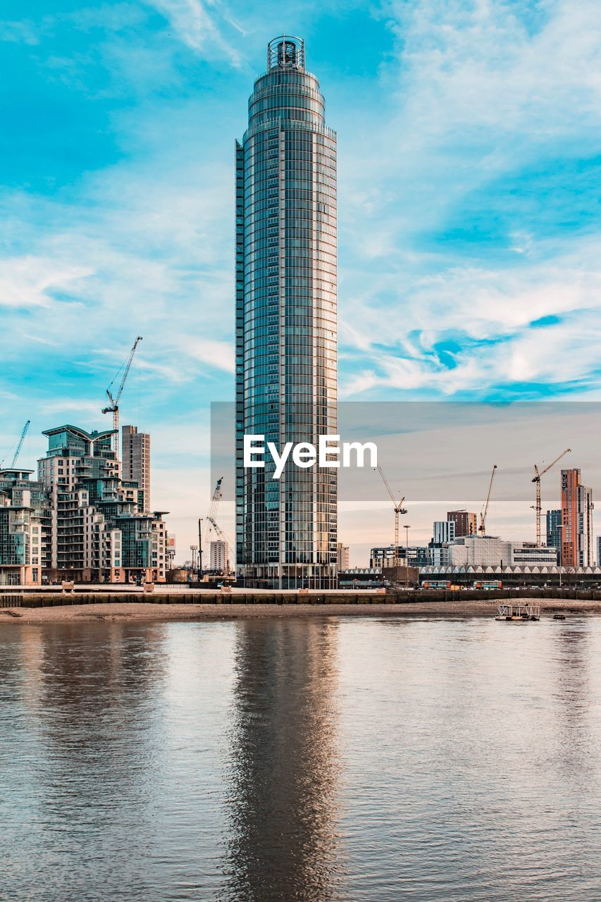 architecture, built structure, sky, skyscraper, building exterior, cloud - sky, development, waterfront, city, crane - construction machinery, modern, water, reflection, no people, travel destinations, day, tall, outdoors, urban skyline