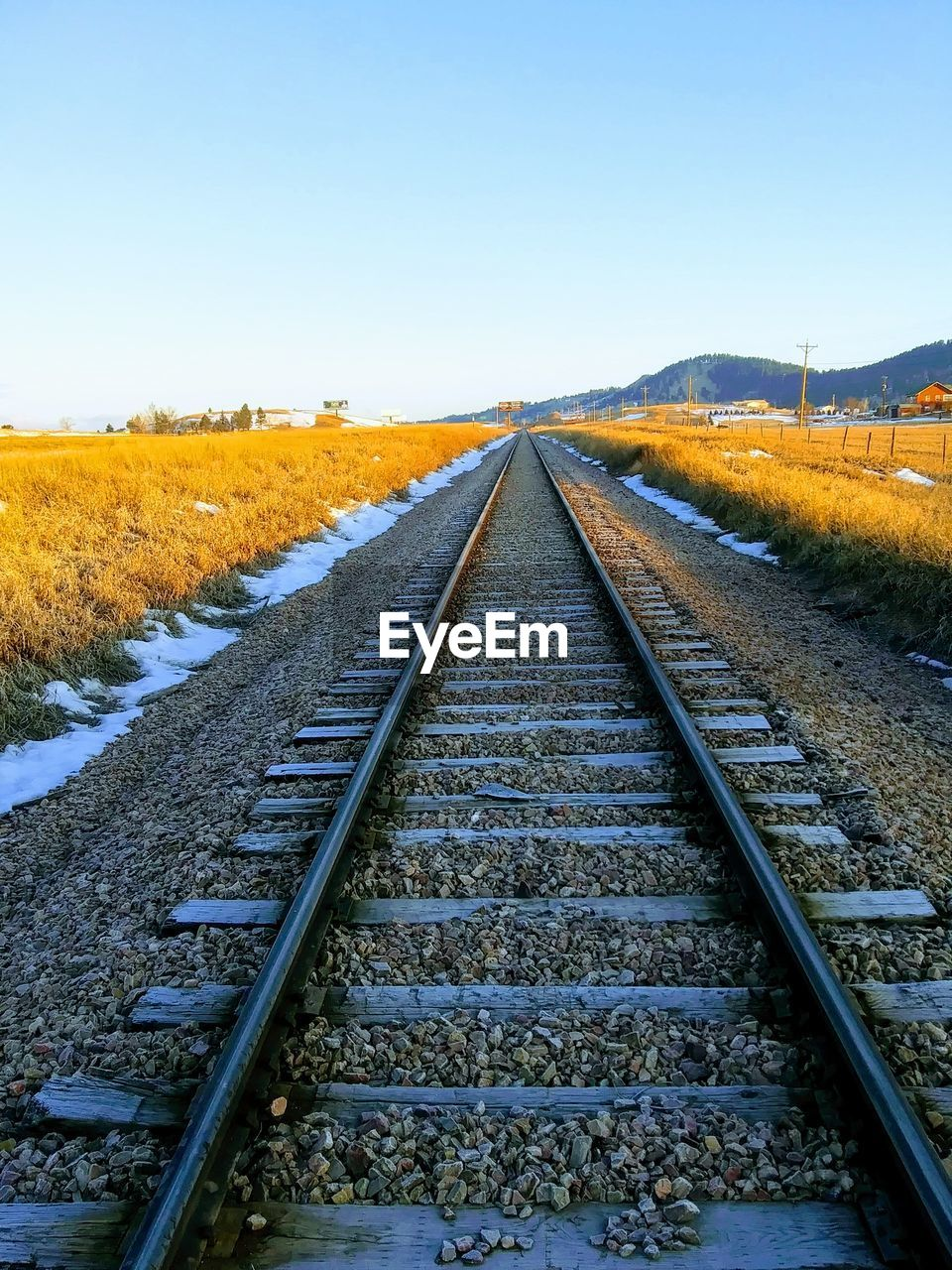 railroad track, rail transportation, track, the way forward, direction, diminishing perspective, sky, transportation, vanishing point, no people, nature, clear sky, plant, day, landscape, tranquil scene, beauty in nature, environment, tranquility, outdoors, parallel, straight, gravel, long
