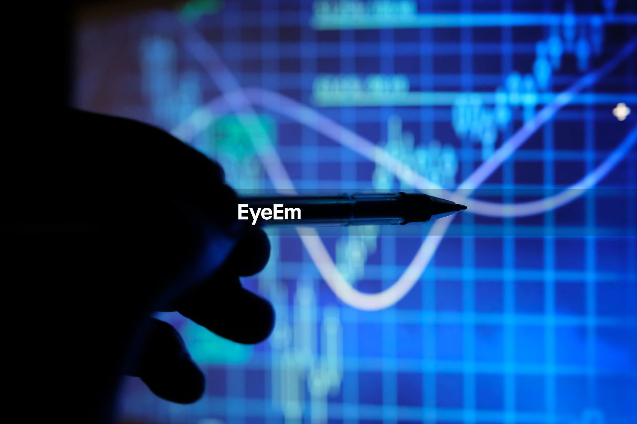 Cropped hand pointing pen to blue graph on computer monitor