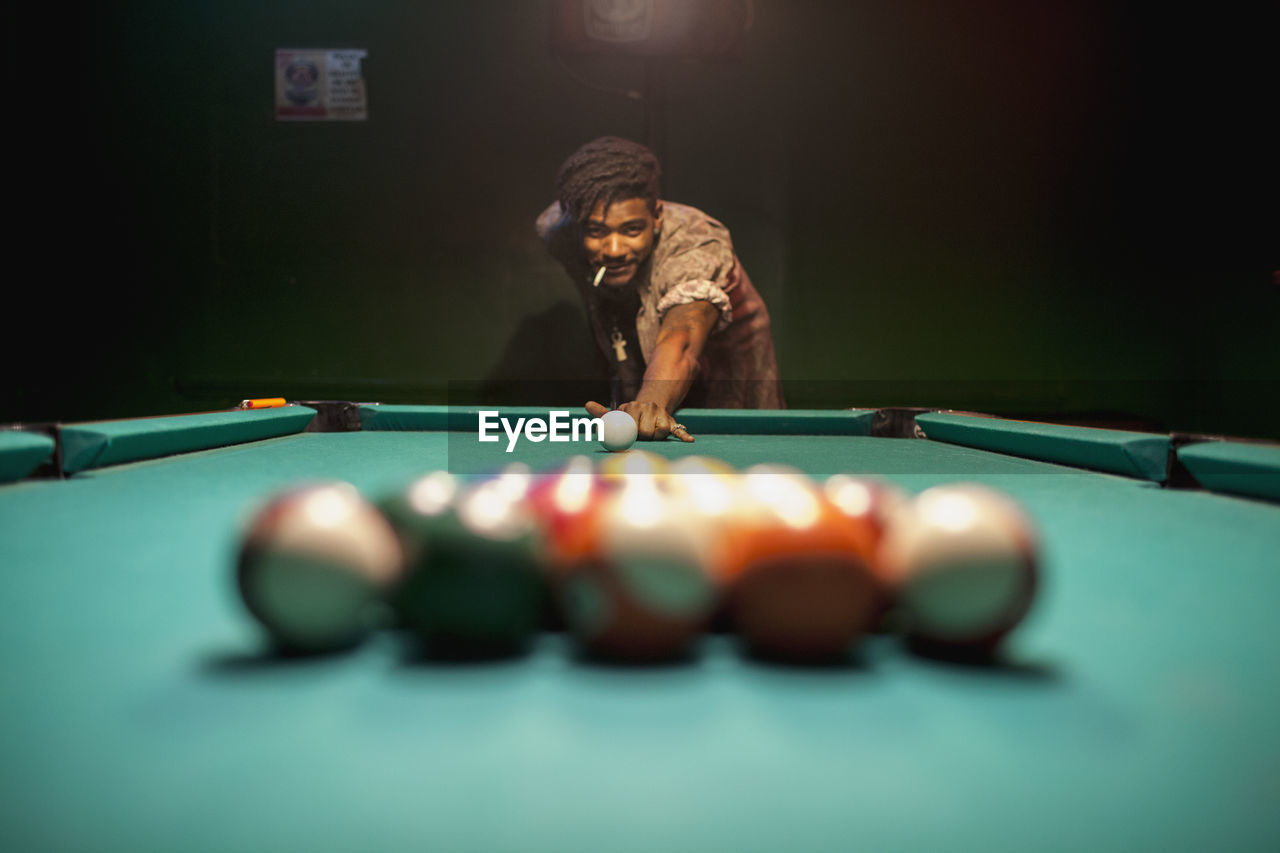 leisure activity, pool ball, table, pool table, pool - cue sport, one person, ball, playing, sport, pool cue, indoors, real people, lifestyles, aiming, concentration, bending, snooker, men, accuracy, skill
