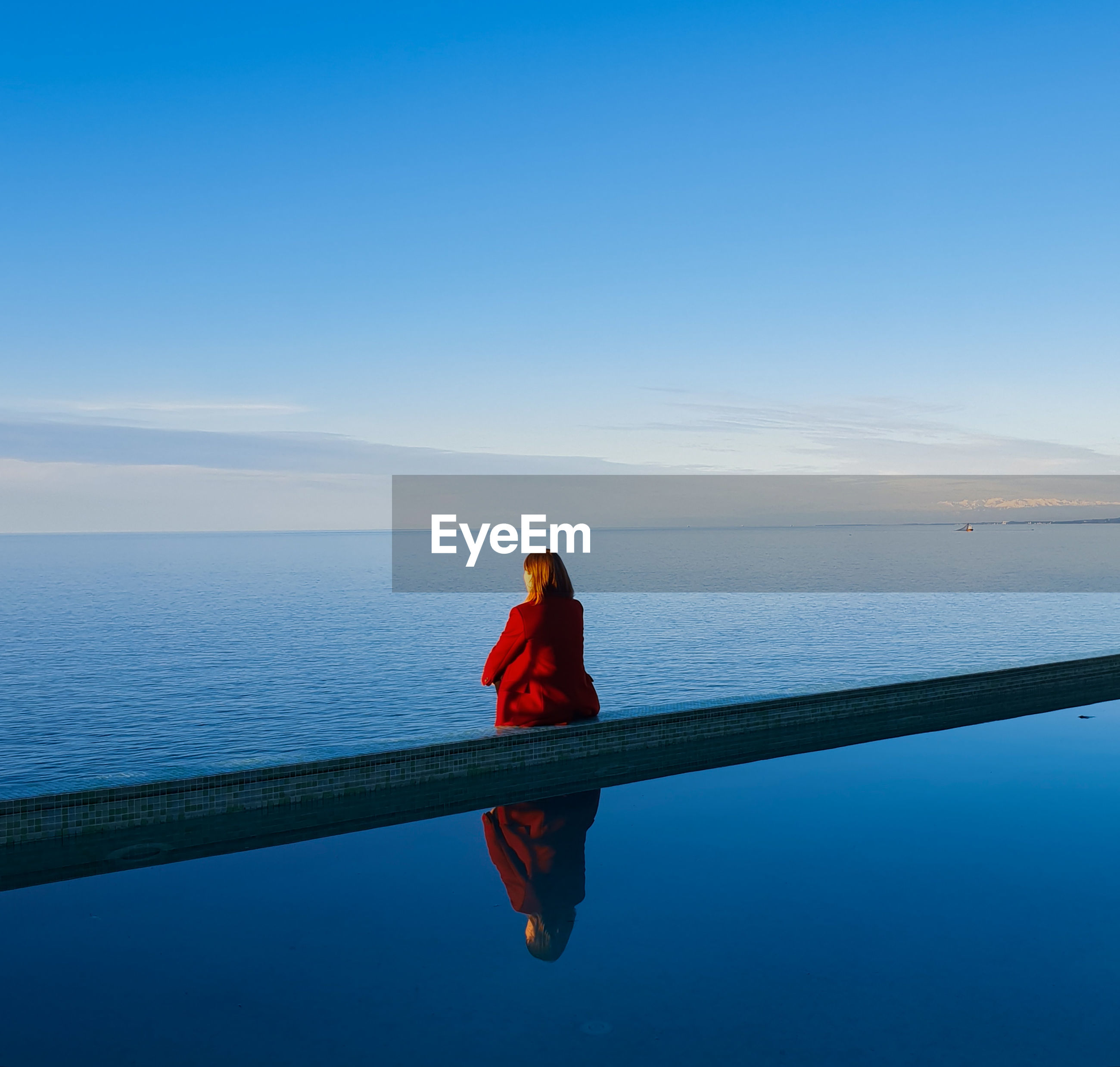Rear view of woman sitting by infinity pool against sea
