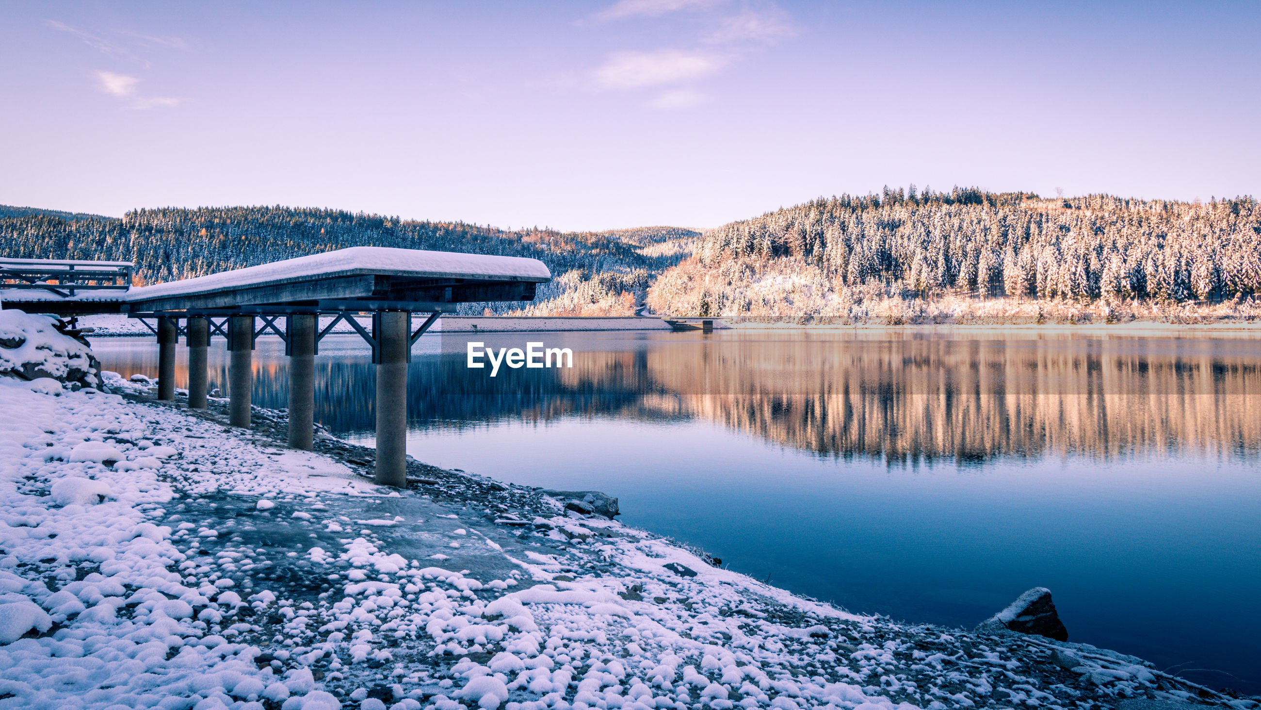 Bridge over river by snowcapped mountains against sky during winter