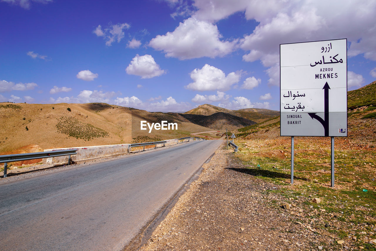 sign, communication, road, sky, transportation, text, western script, road sign, cloud - sky, direction, nature, day, the way forward, information, no people, guidance, land, symbol, information sign, mountain, outdoors, diminishing perspective
