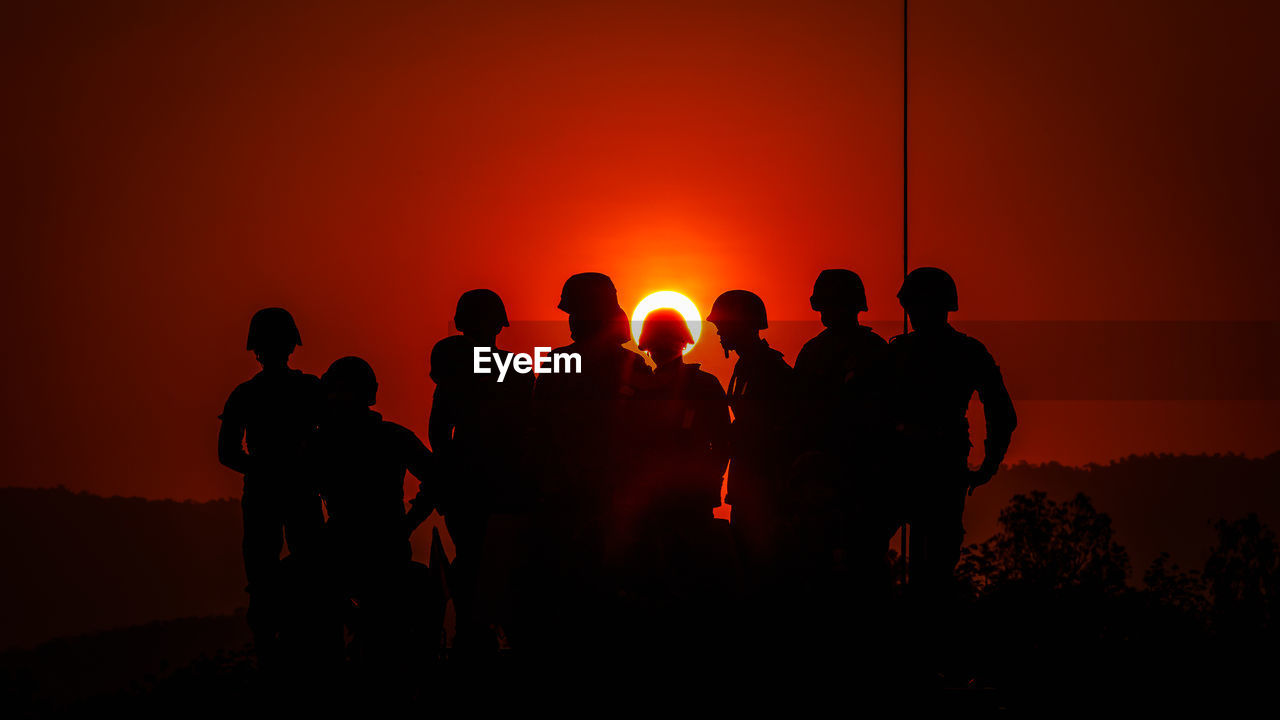 Silhouette Army Soldiers Against Sky During Sunset