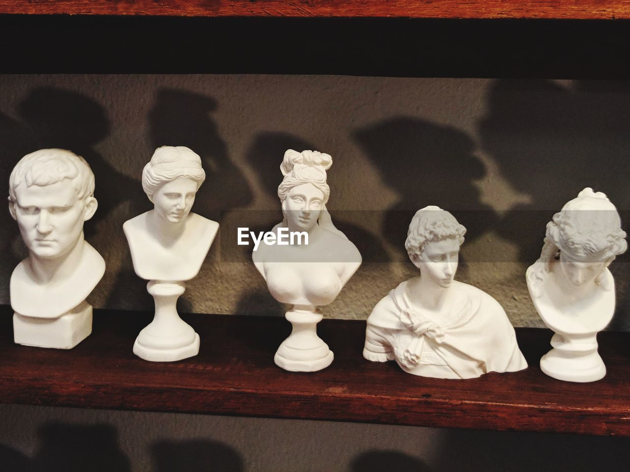 representation, human representation, indoors, no people, art and craft, male likeness, still life, table, side by side, close-up, female likeness, creativity, sculpture, in a row, variation, wood - material, bust, statue, arrangement, store, retail display