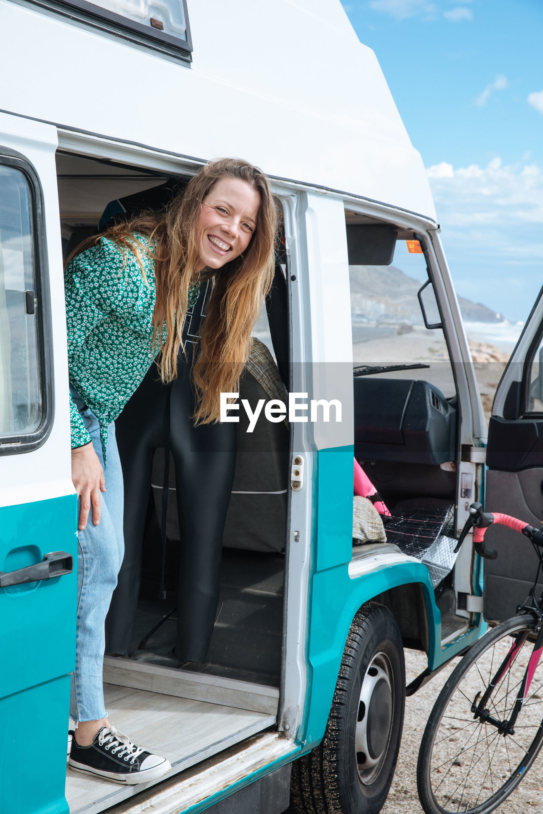 Woman standing at entrance of camper van