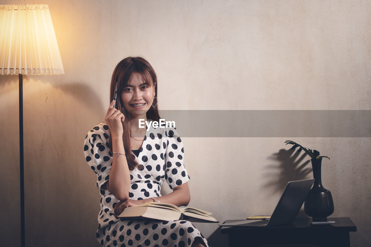 one person, technology, front view, indoors, sitting, young adult, casual clothing, wireless technology, real people, portrait, wall - building feature, adult, women, communication, looking at camera, lighting equipment, hairstyle, laptop, lifestyles, electric lamp, using laptop, bangs, polka dot