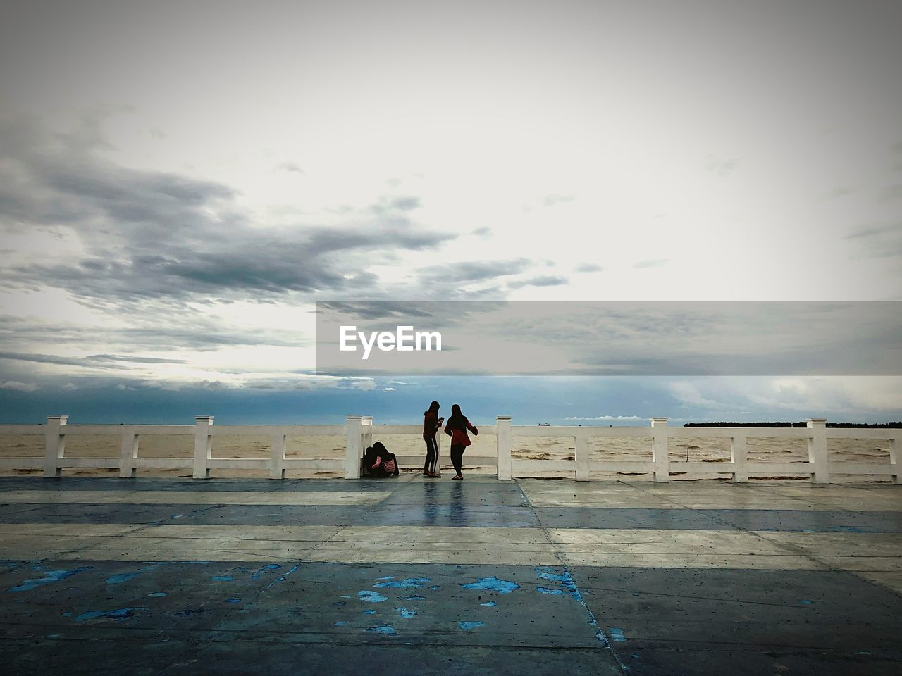 REAR VIEW OF COUPLE WALKING ON SHORE AGAINST SKY