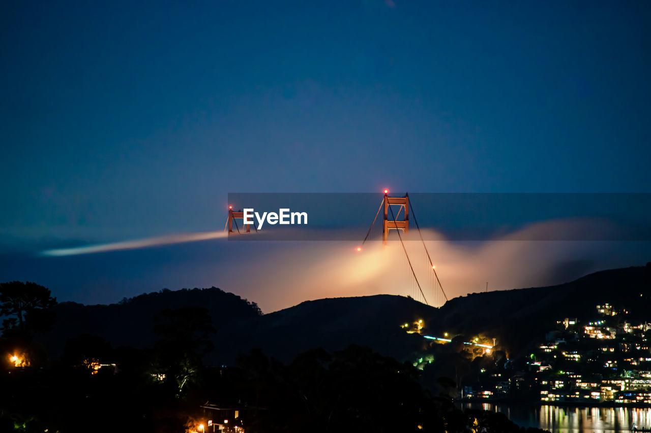 Illuminated bridge over silhouette buildings in city at night