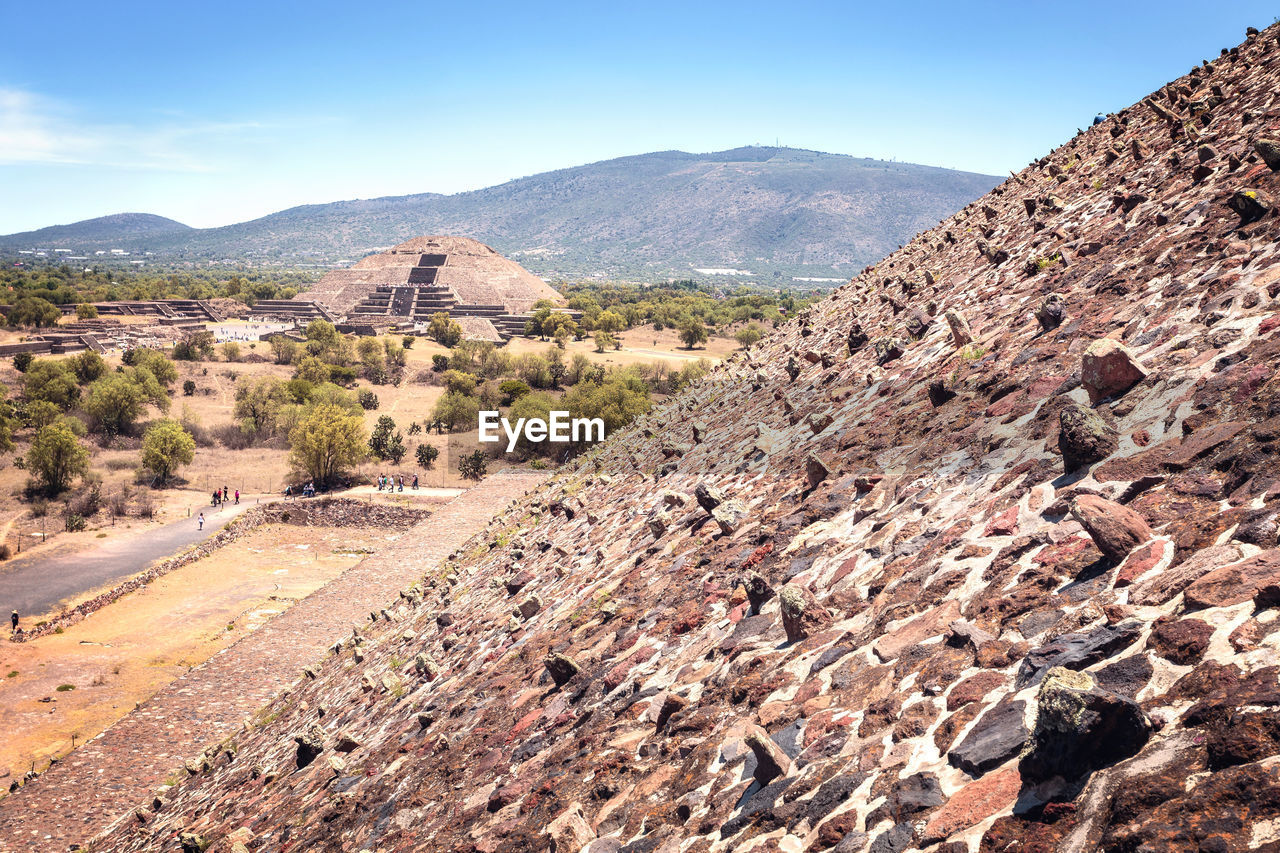 mountain, sky, environment, architecture, scenics - nature, nature, built structure, landscape, day, mountain range, tranquil scene, history, no people, the past, travel destinations, travel, tranquility, sunlight, beauty in nature, tourism, outdoors, climate, ancient civilization, arid climate