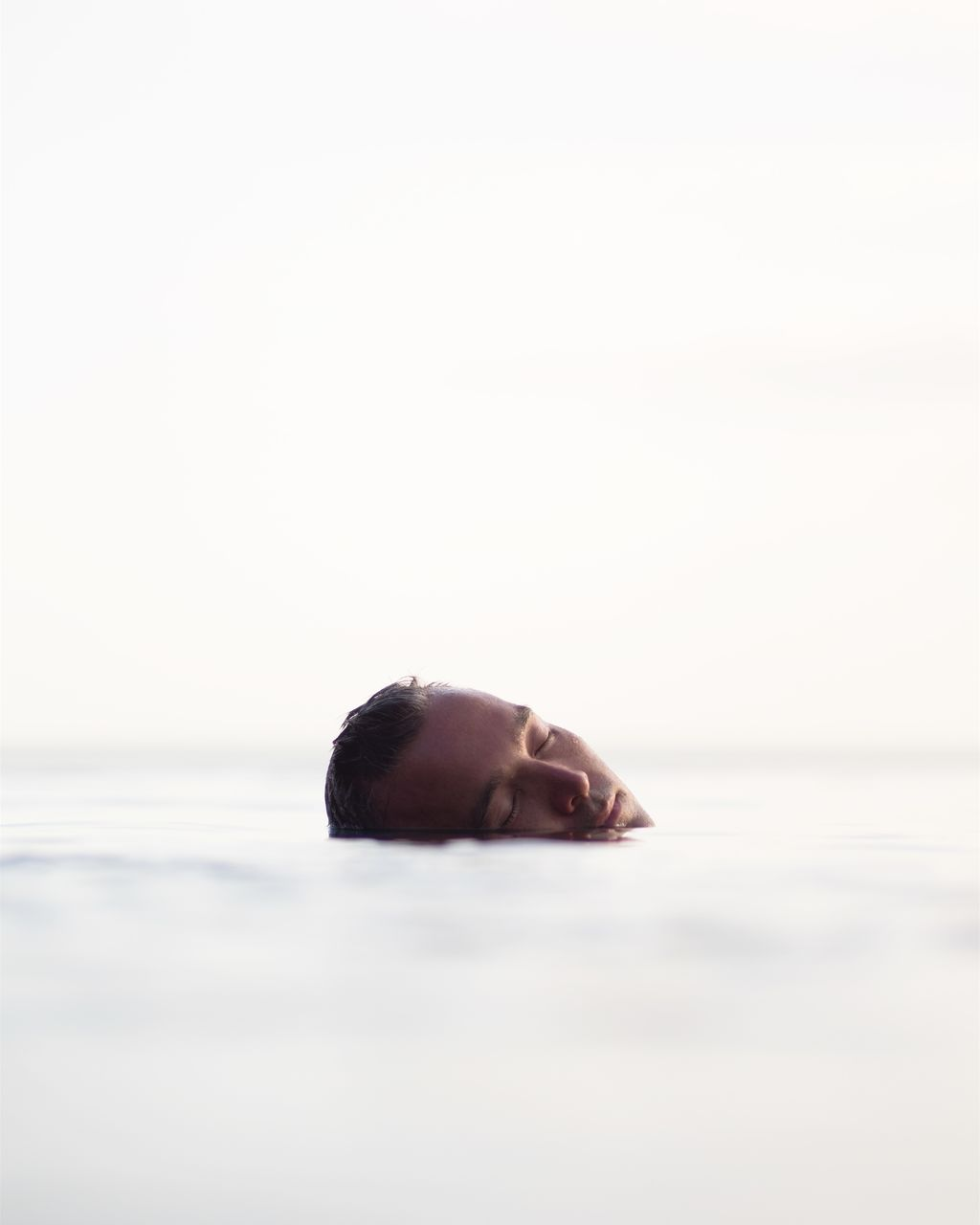 Man with eyes closed swimming in sea against clear sky