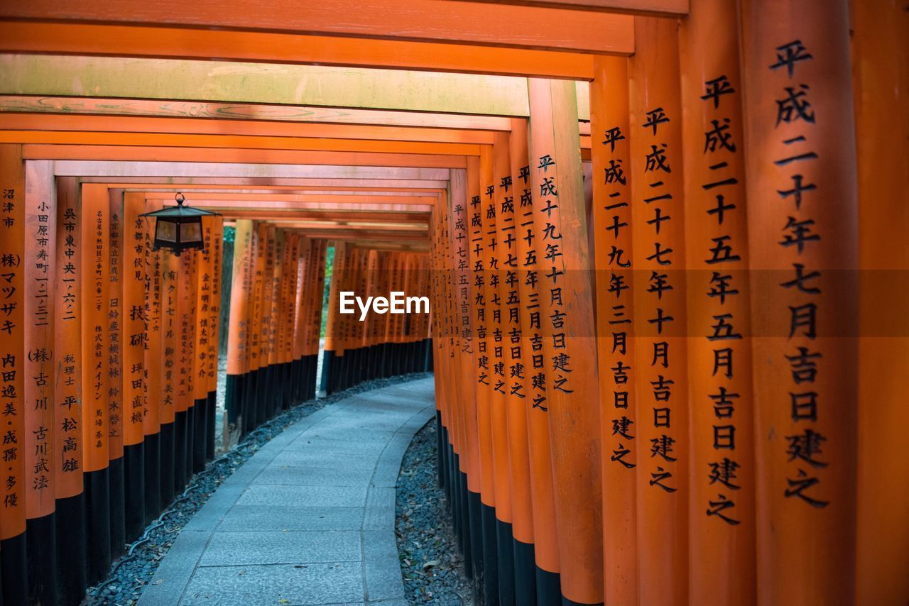 place of worship, text, religion, orange color, spirituality, shrine, architecture, travel destinations, architectural column, the way forward, communication, built structure, day, no people, outdoors