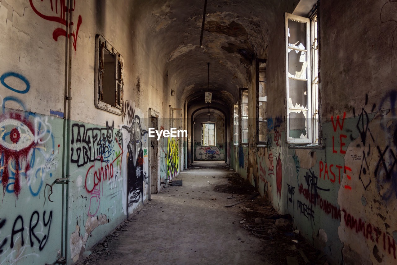 architecture, built structure, building, graffiti, direction, the way forward, abandoned, wall - building feature, text, no people, indoors, corridor, arcade, day, old, wall, empty, art and craft, diminishing perspective, deterioration, ruined, alley