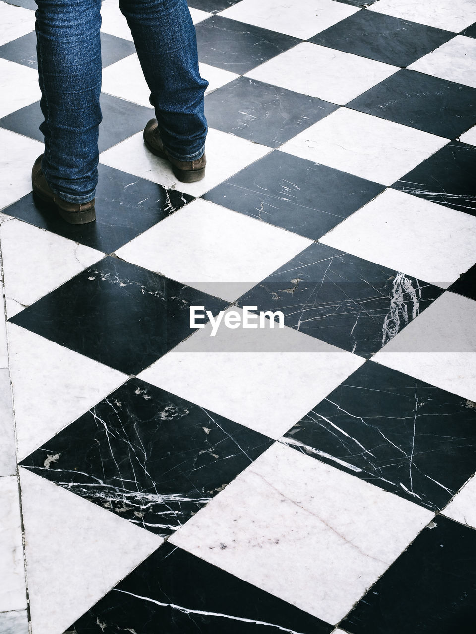 Low Section Of Man Standing On Checked Floor