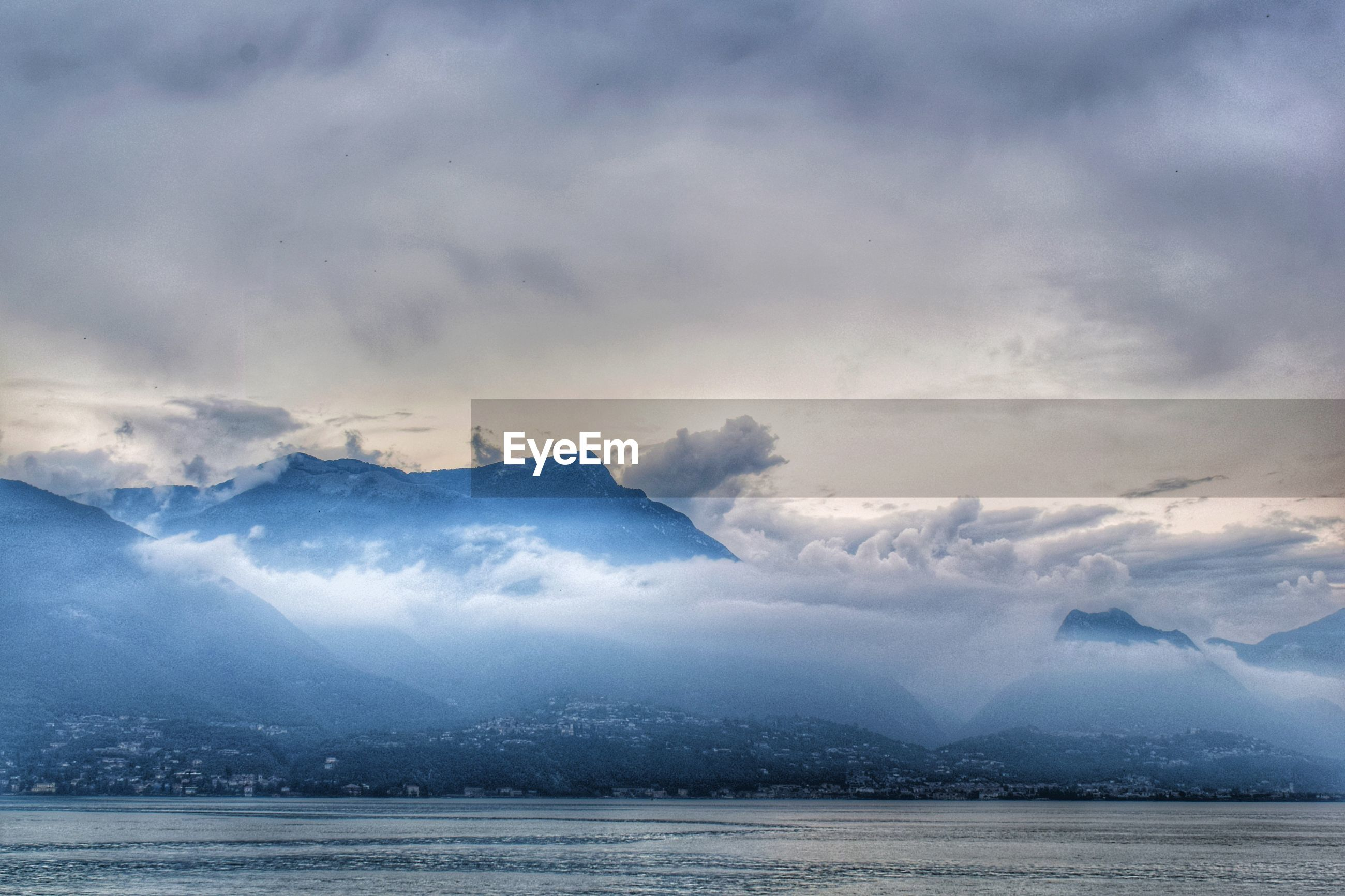 Scenic view of sea and cloud mountains against sky before thunderstorm