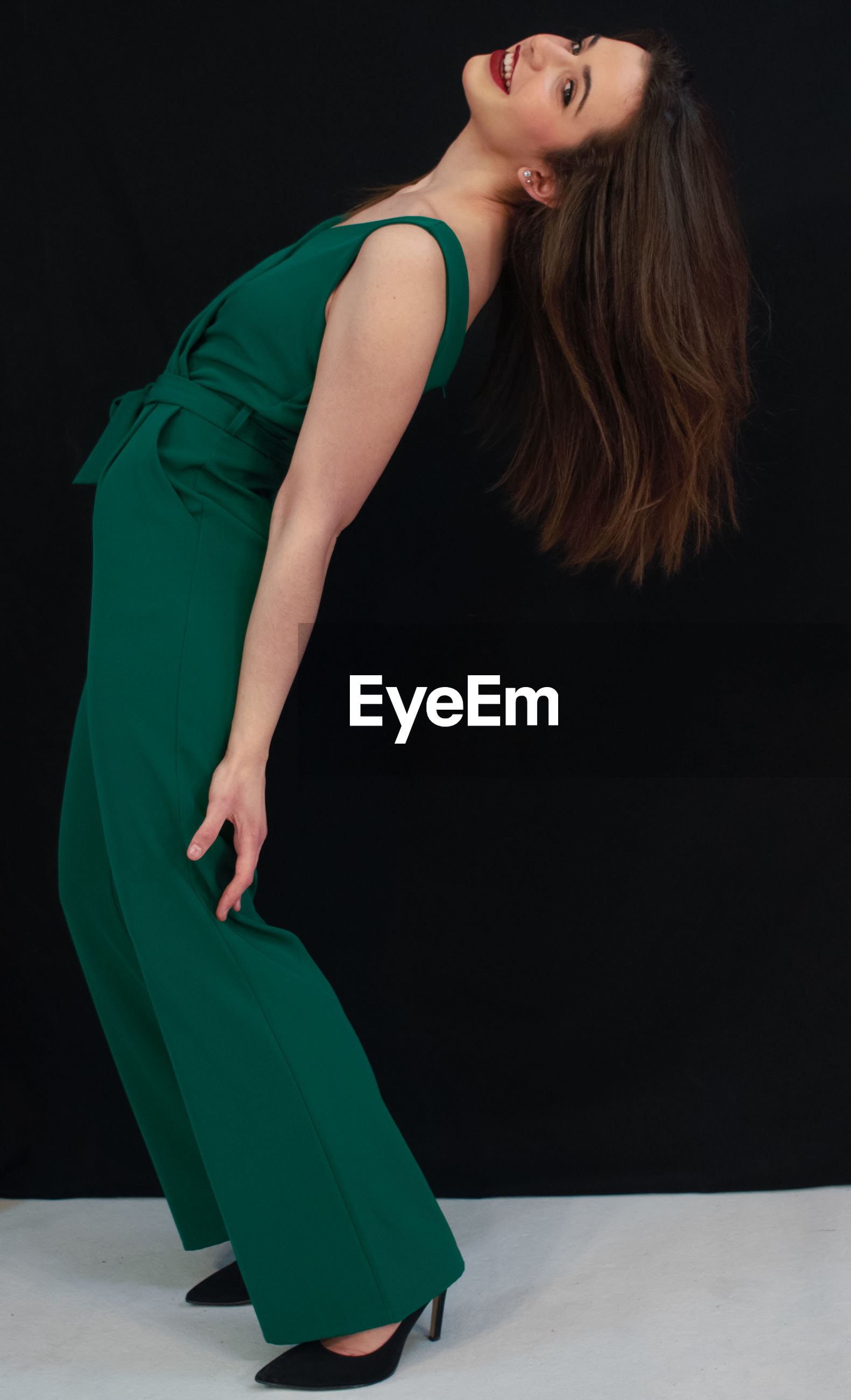 Full length of woman standing against black background