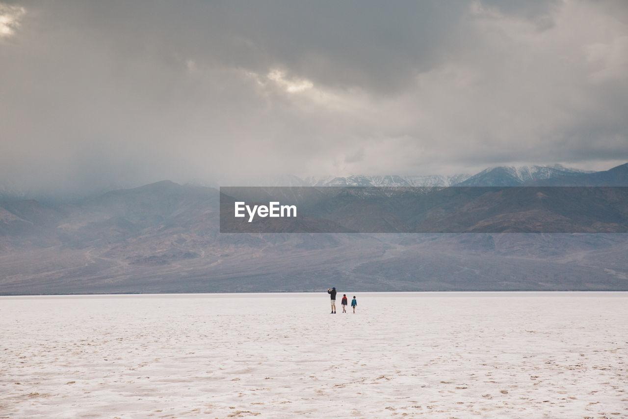 People Walking On Desert Against Sky