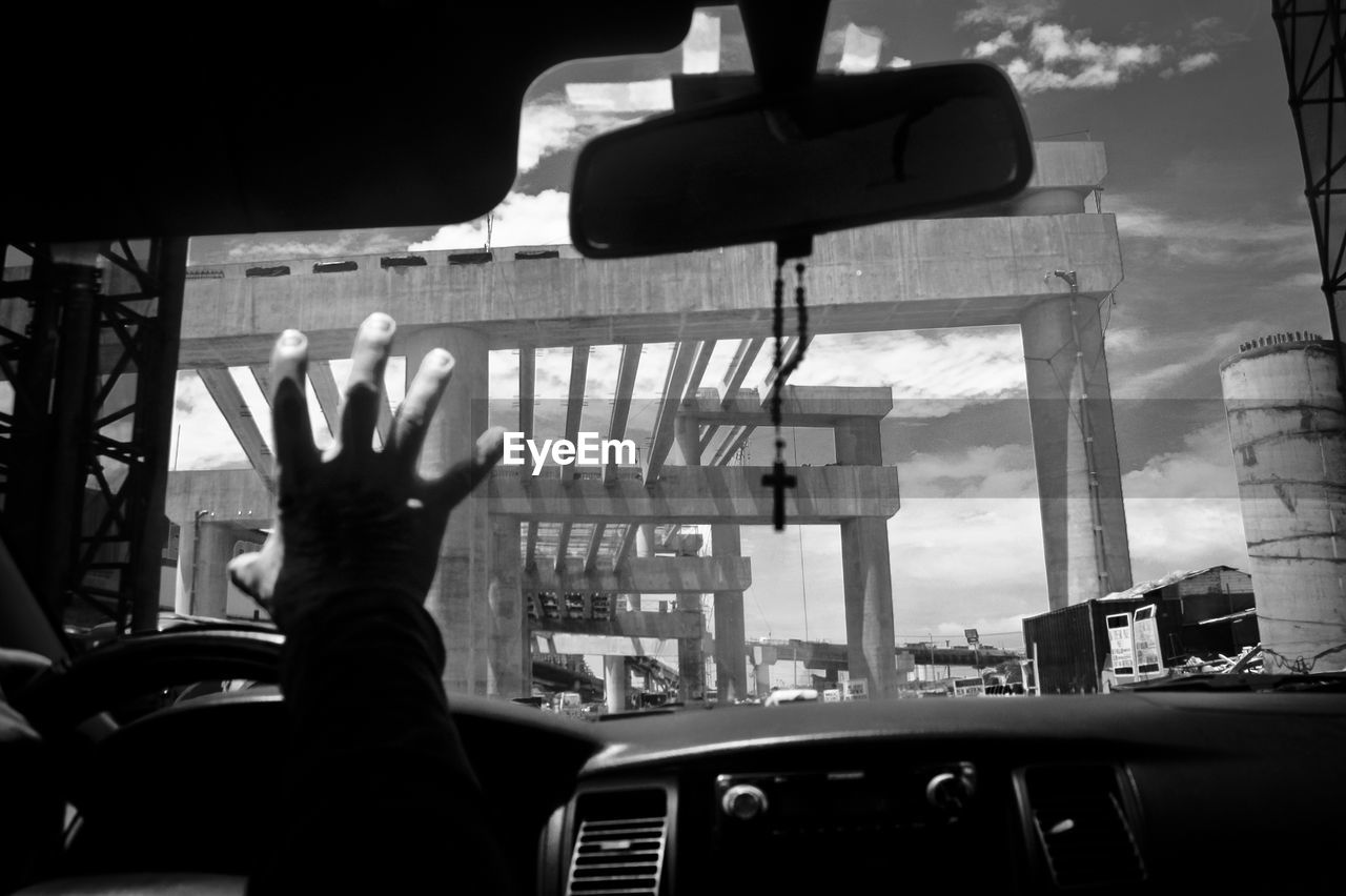 Cropped image of hand raised while driving car