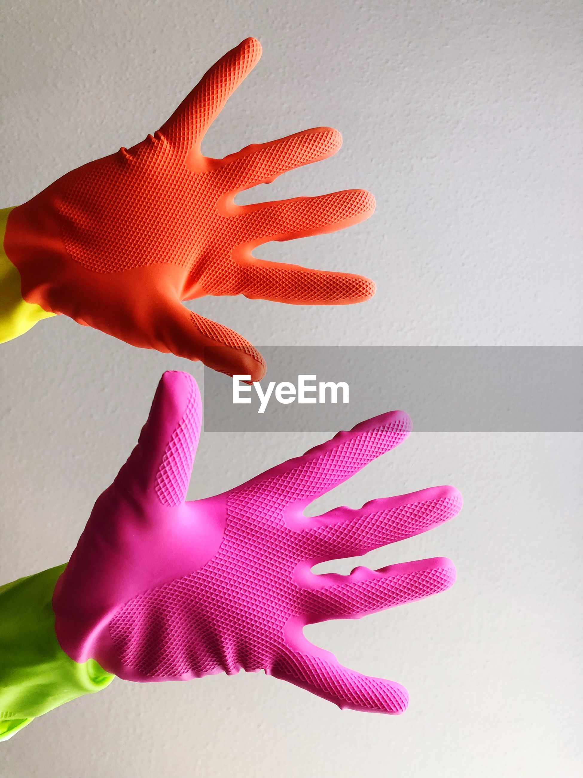 Close-up of hands wearing gloves against wall