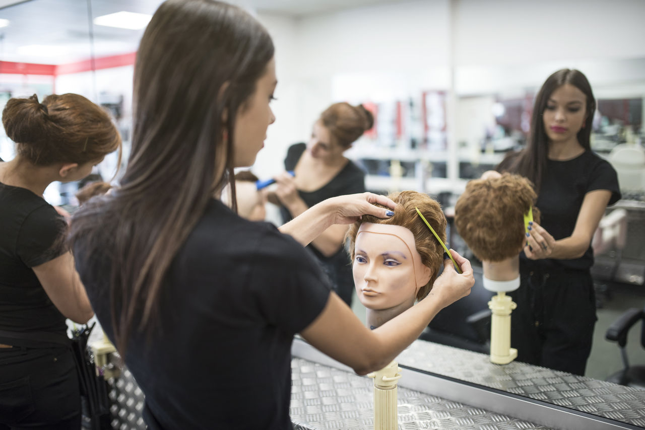 Hairdressers practicing on mannequin at barber shop