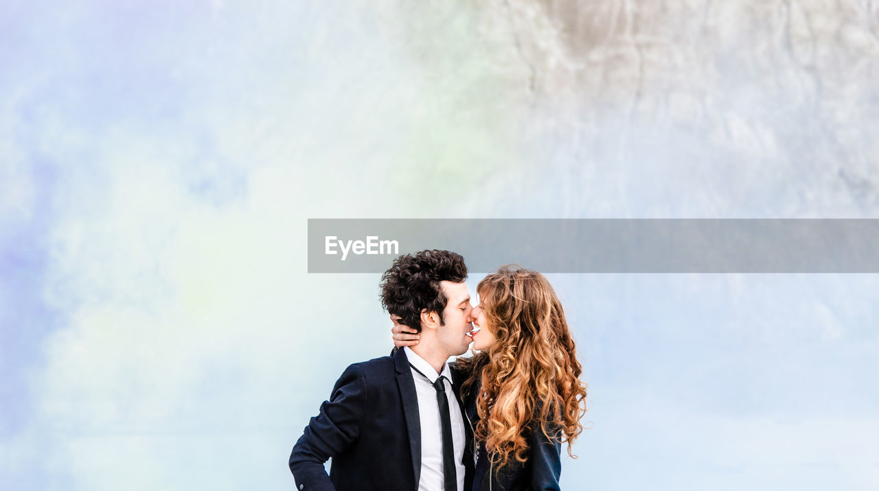 Young Couple Kissing Against Smoke