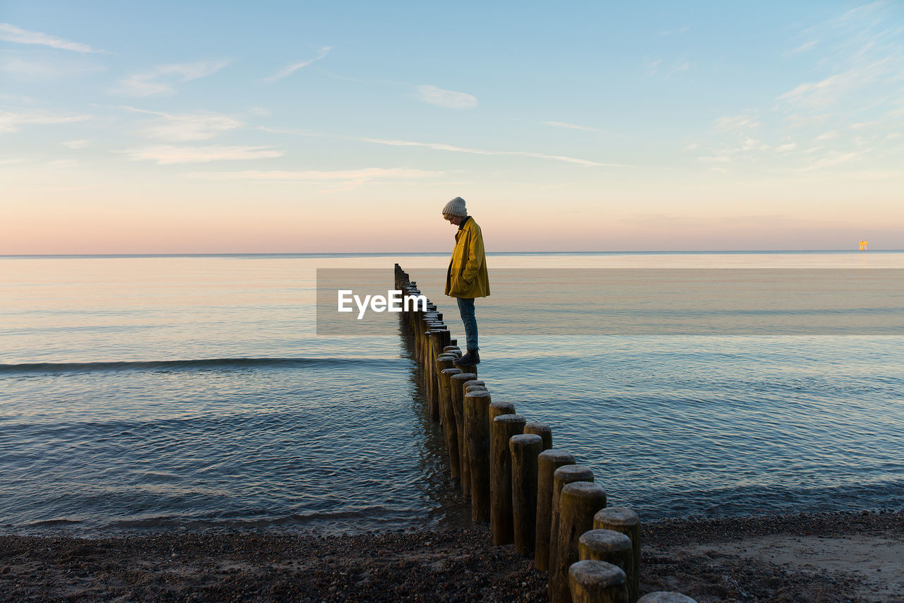 sea, water, horizon over water, tranquil scene, scenics, tranquility, beauty in nature, nature, sky, idyllic, wooden post, no people, outdoors, sunset, beach, day, groyne, perching, bird