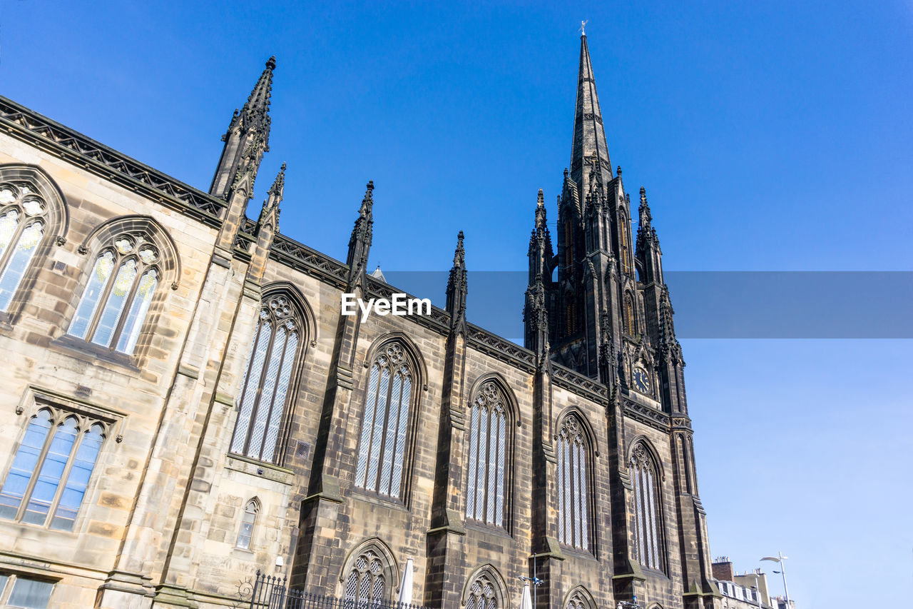 religion, spirituality, place of worship, architecture, built structure, low angle view, building exterior, rose window, history, travel destinations, gothic style, day, outdoors, blue, no people, sky