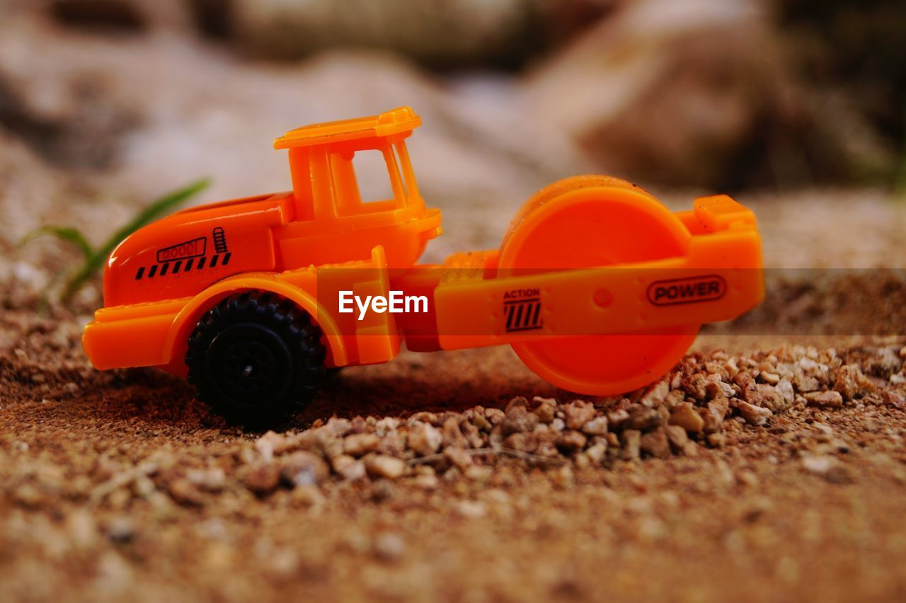 toy, orange color, toy car, selective focus, plastic, no people, red, day, close-up, childhood, outdoors, yellow