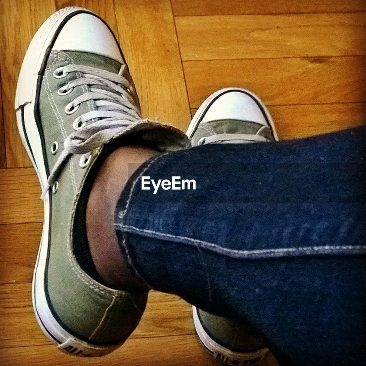 human leg, shoe, low section, jeans, human body part, one person, real people, human foot, personal perspective, canvas shoe, indoors, casual clothing, standing, lifestyles, leisure activity, hardwood floor, skateboard, directly above, close-up, high angle view, fashion, men, day, human hand, skateboard park, adult, people