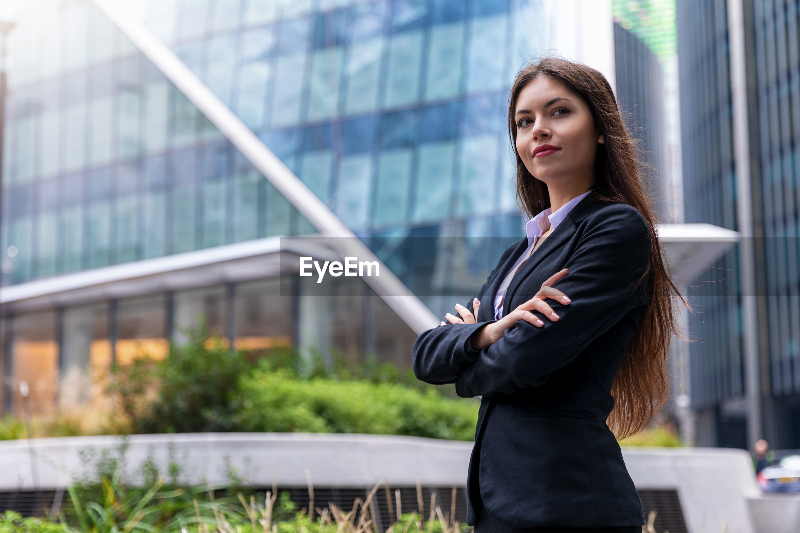 Confident businesswoman with arms crossed standing in city