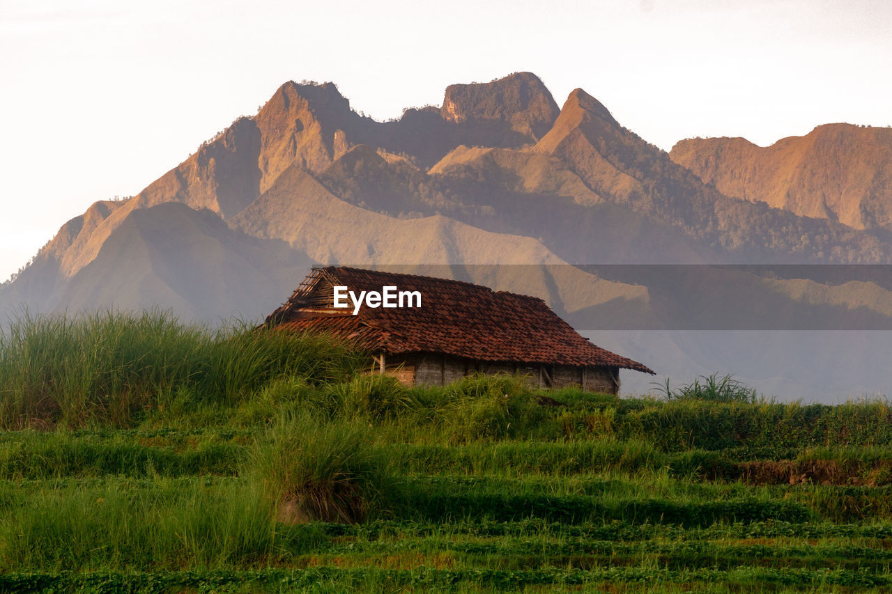 House on field by mountains against sky