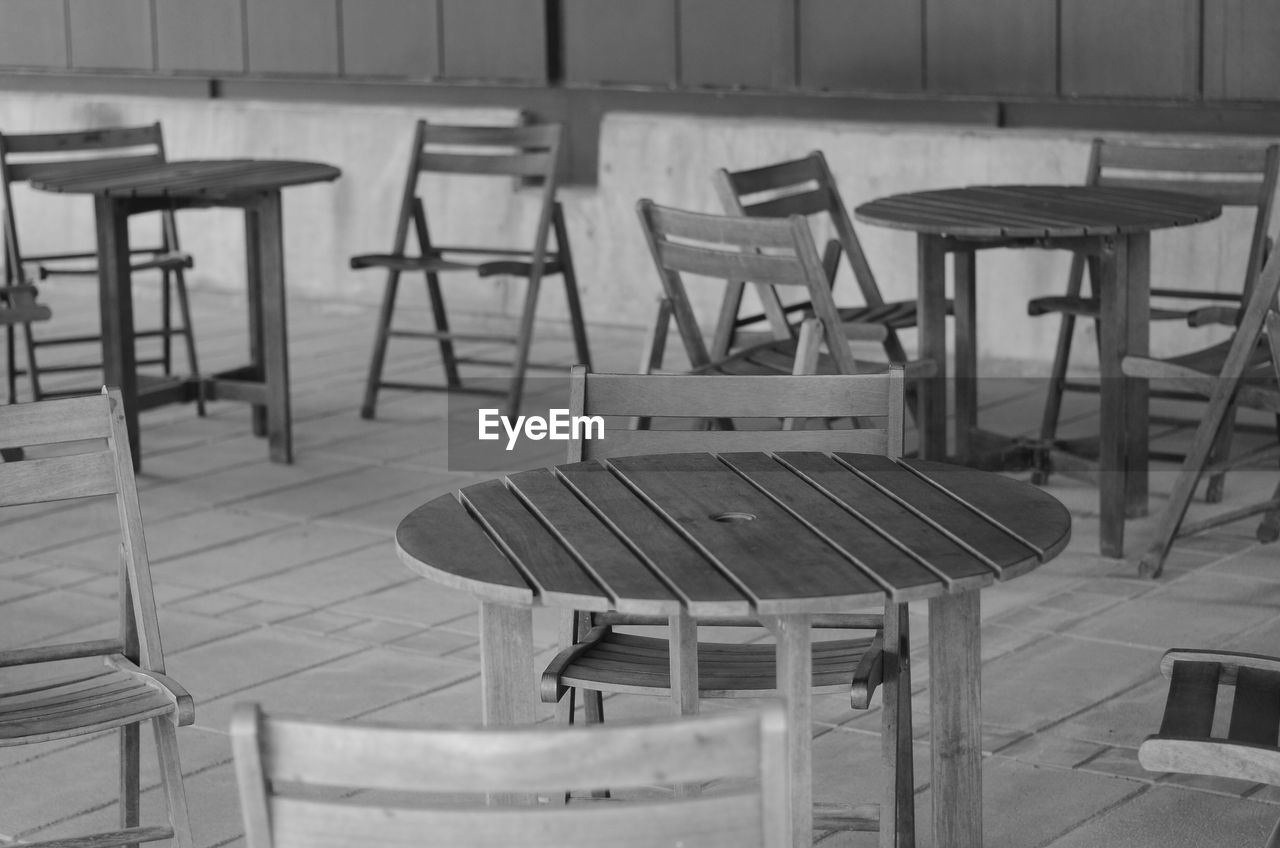 seat, chair, empty, table, absence, wood - material, furniture, no people, restaurant, indoors, flooring, cafe, arrangement, business, focus on foreground, day, architecture, sidewalk cafe, still life, setting