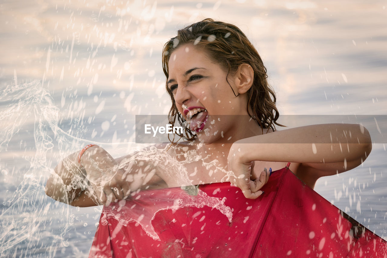 one person, real people, happiness, motion, leisure activity, water, smiling, lifestyles, enjoyment, young adult, women, nature, portrait, young women, focus on foreground, splashing, front view, outdoors, beautiful woman, hairstyle, spraying, wet hair