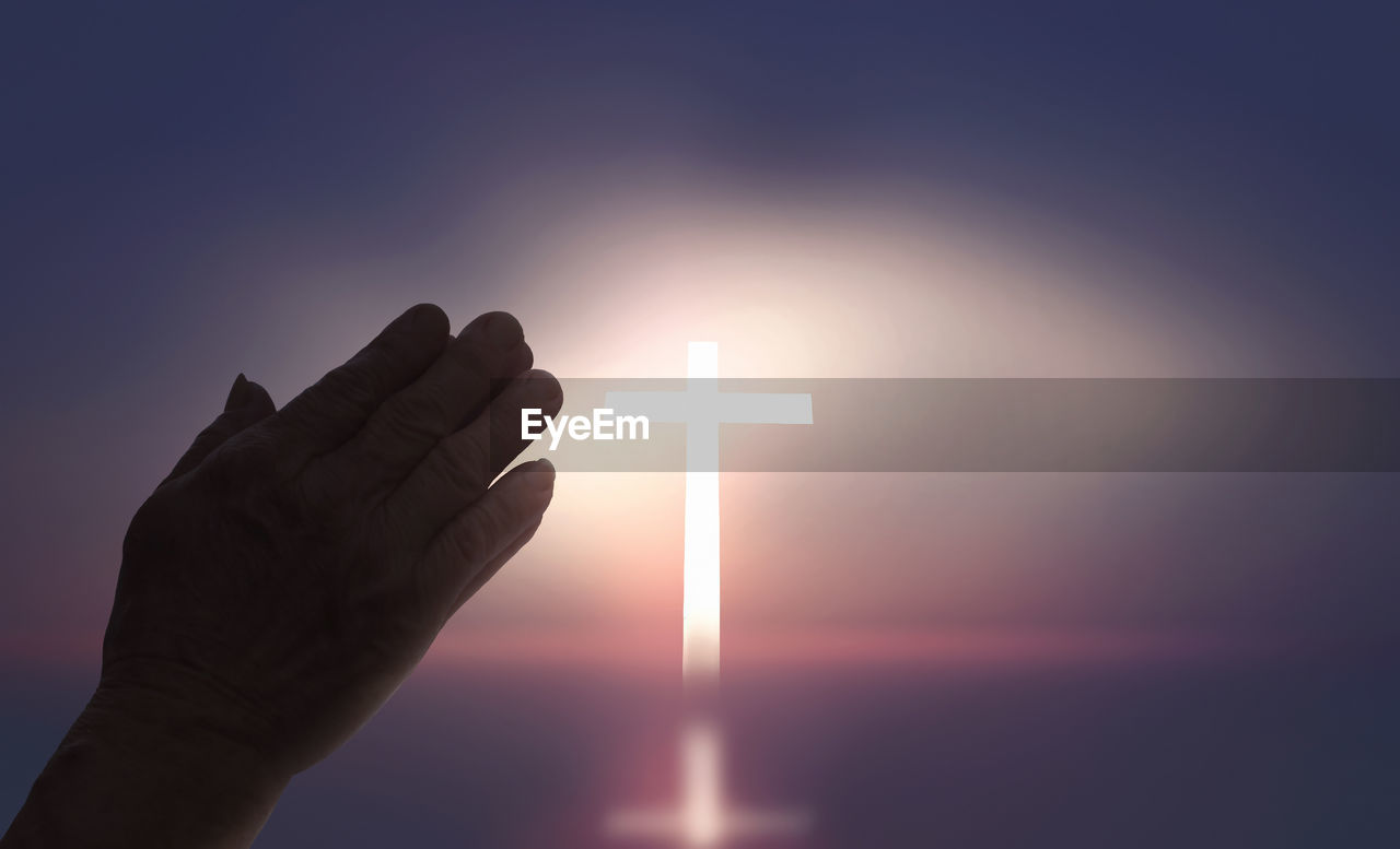 human hand, hand, human body part, sky, finger, human finger, sunset, unrecognizable person, one person, body part, sun, holding, real people, lifestyles, nature, glowing, illuminated, lens flare, personal perspective, cross, eclipse