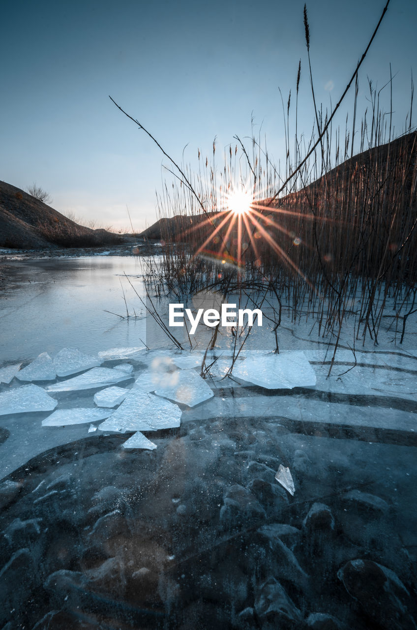 cold temperature, winter, water, snow, frozen, ice, sky, lake, nature, tranquility, beauty in nature, tranquil scene, scenics - nature, sunset, no people, sun, cold, frost, outdoors, frozen water, icicle