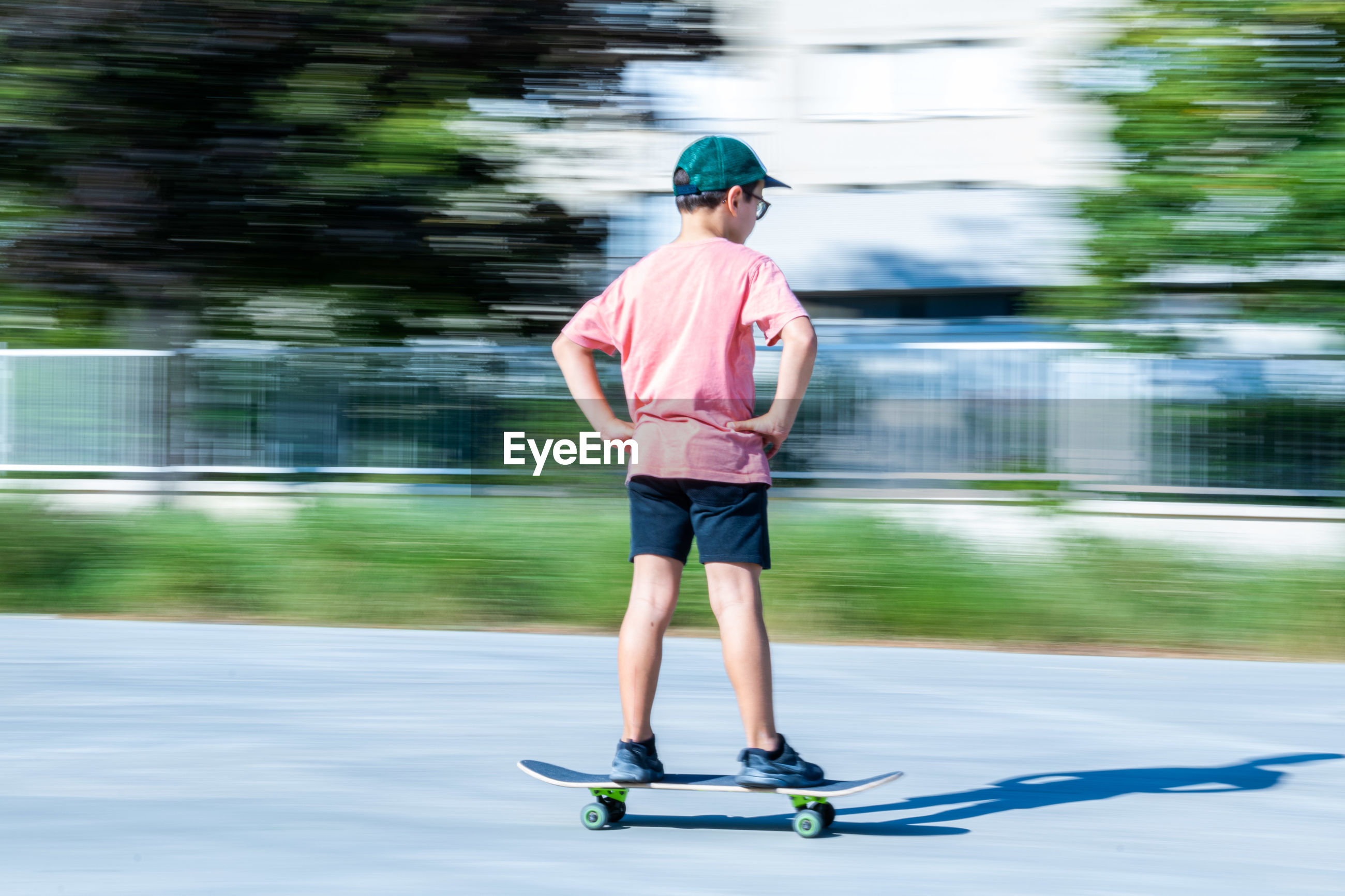 Full length rear view of boy skateboarding on road