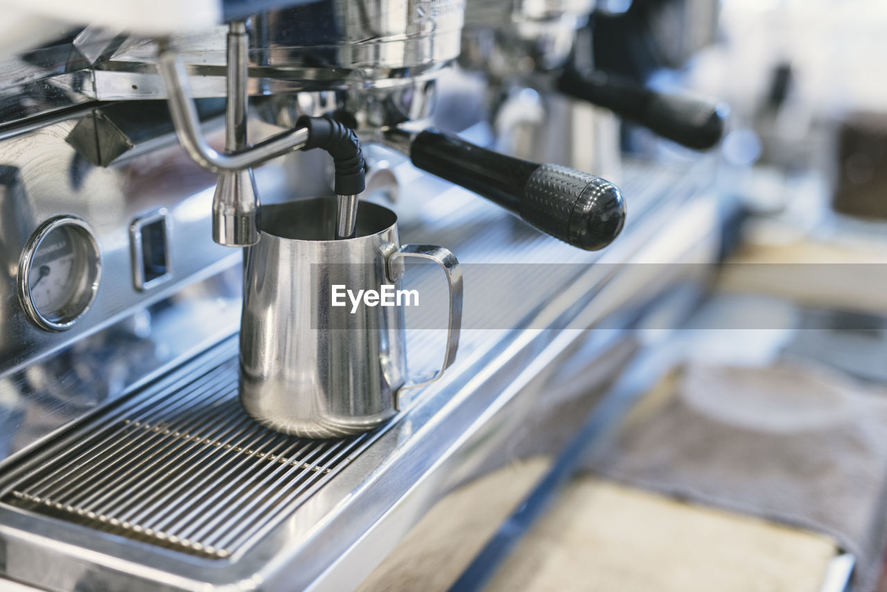 High Angle View Of Pitcher In Espresso Maker At Cafe