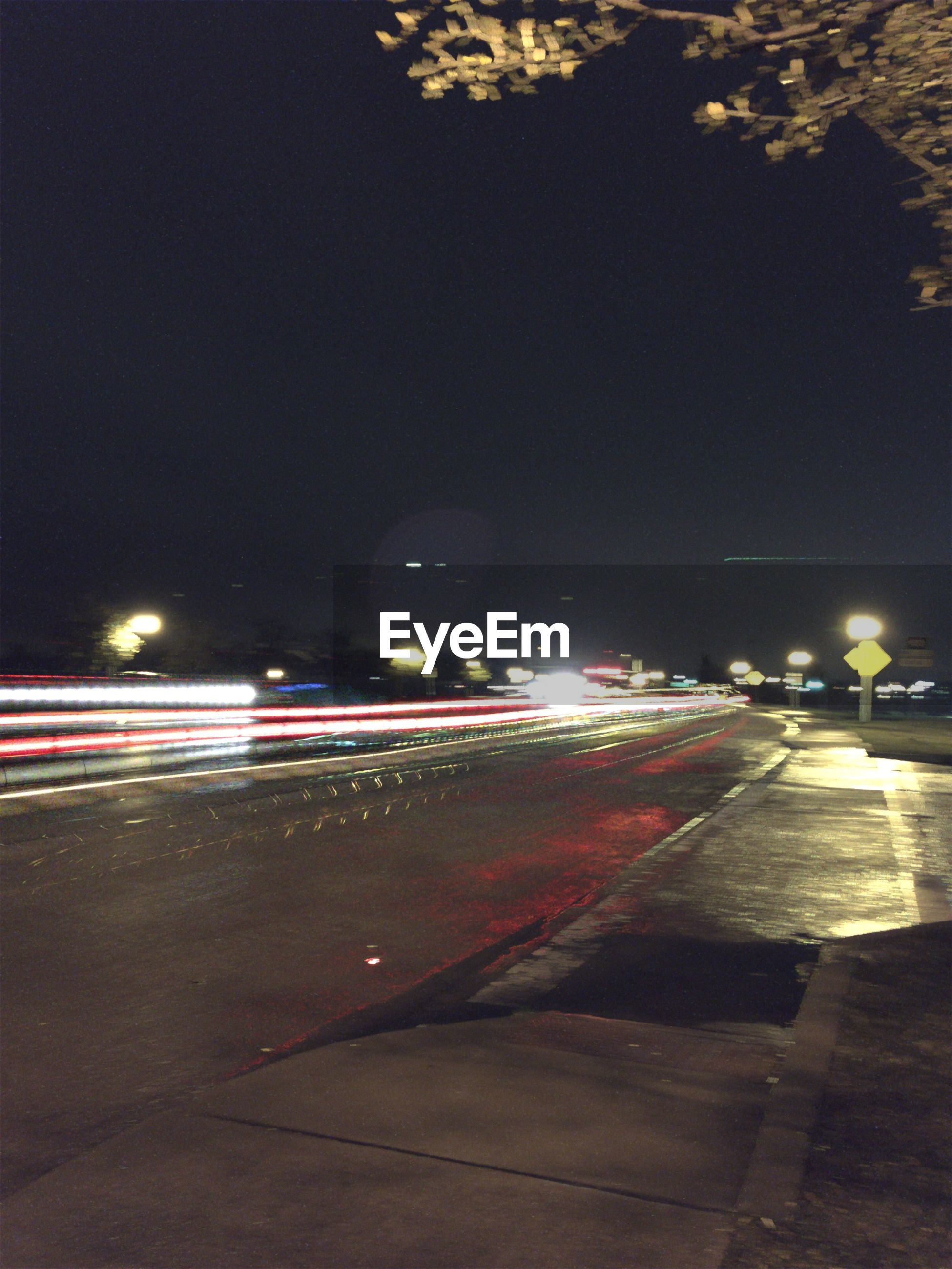 Light trails of street against clear sky at night