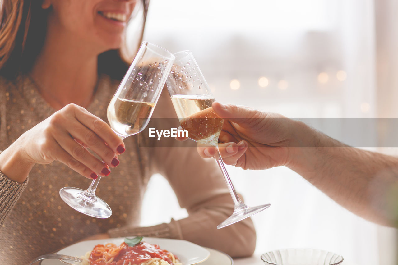 food and drink, glass, alcohol, human hand, celebration, hand, holding, real people, refreshment, drink, women, lifestyles, adult, togetherness, wine, friendship, leisure activity, focus on foreground, human body part, men, celebratory toast