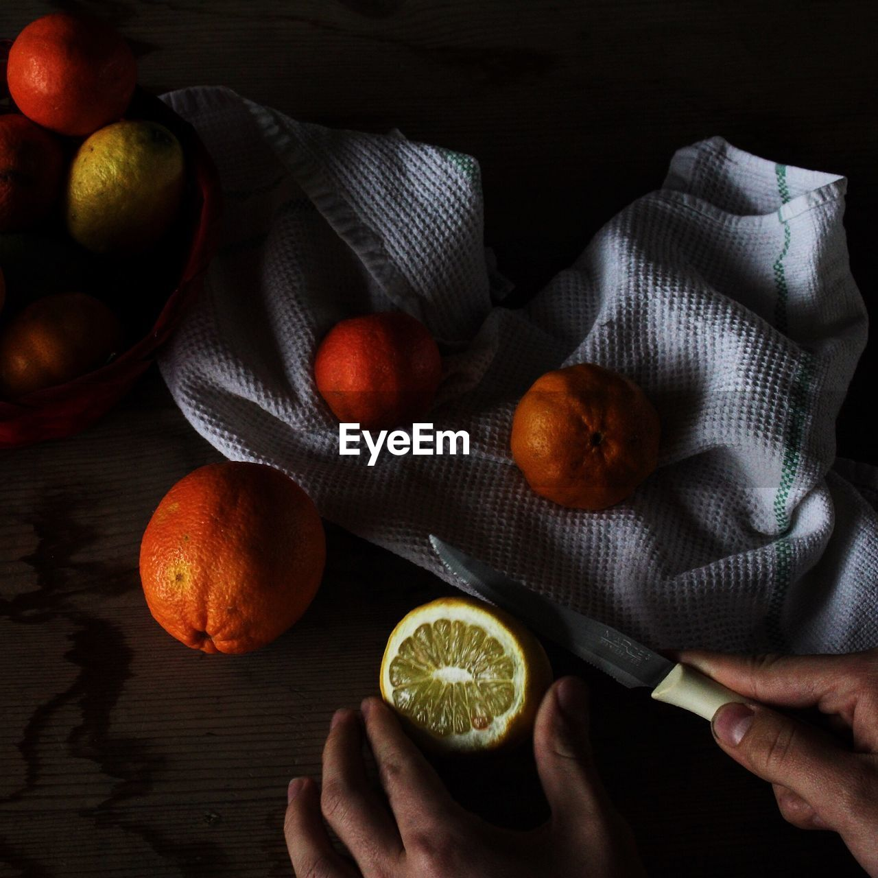 Cropped Imaged Of Person Cutting Oranges On Table