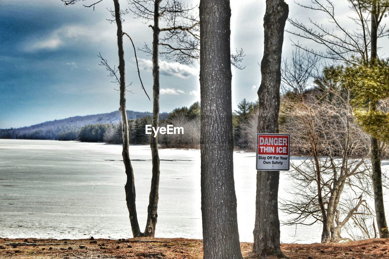 Warning signboard on tree trunk against calm lake