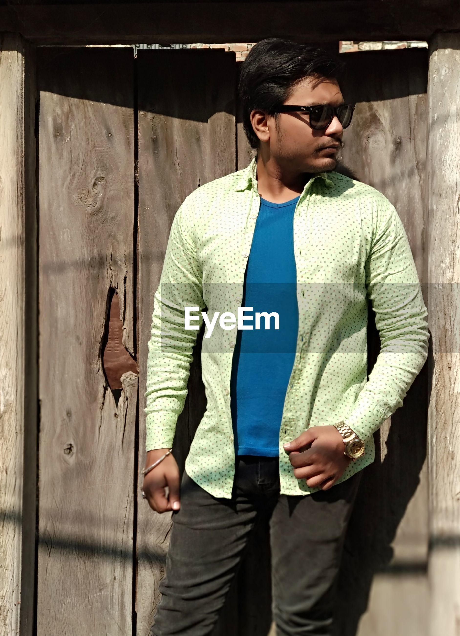 Young man in sunglasses standing against wall
