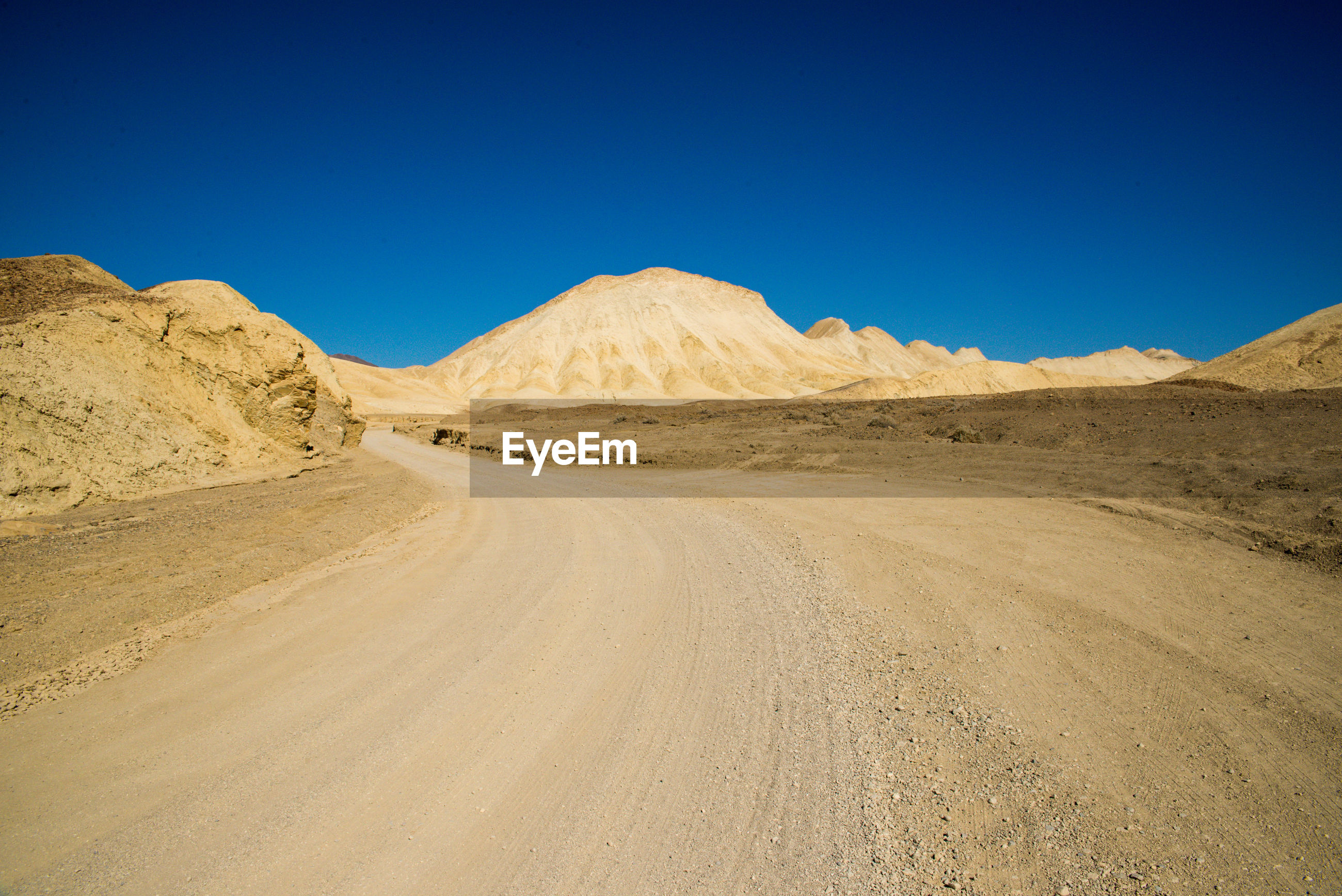 Scenic view of desert road against clear blue sky