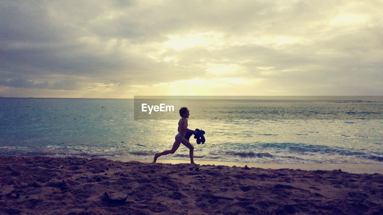 Boy Running On Shore At Beach During Sunset